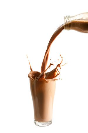 Het gieten van chocolade melk van fles in glas met spatten., Geïsoleerde witte achtergrond.