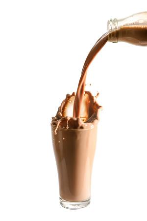 verre de lait: Verser le lait au chocolat de la bouteille en verre avec des éclaboussures., Fond blanc isolé. Banque d'images