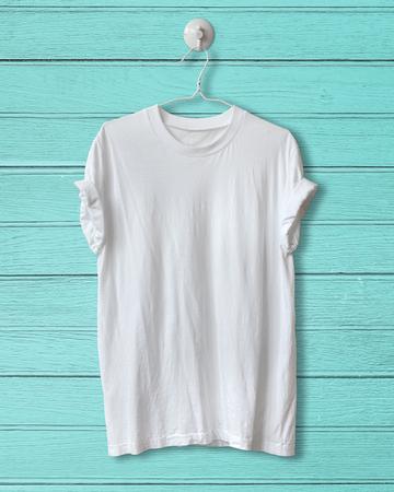 t-shirt blanc pendre sur bois bleu vintage background.