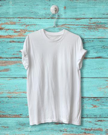 White t-shirt hang on blue wood vintage background. Imagens