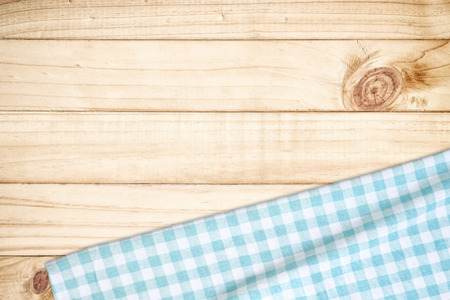 Blue tablecloth on wooden table with copy space.