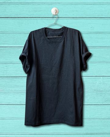 cotton fabric: Black blank T-shirt hang on wood wall. Stock Photo