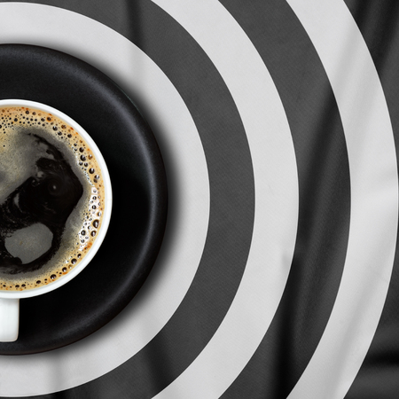 punctuate: Top view of coffee cup put on a tablecloth., Tablecloth circle pattern punctuate black and white. Stock Photo