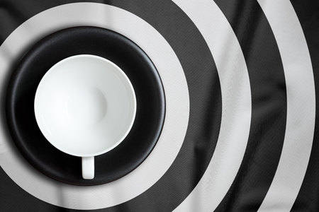 punctuate: Top view of blank coffee cup put on a tablecloth., Tablecloth circle pattern punctuate black and white.