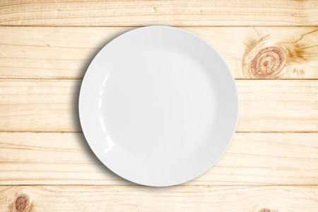clean dishes: Blank white dish on a wood background.