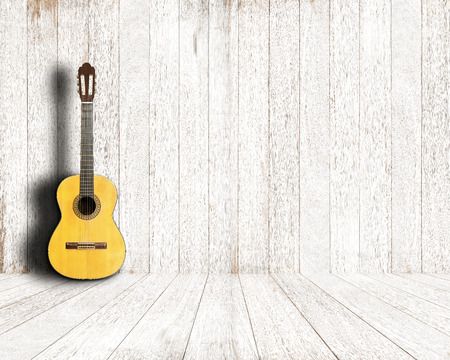 Classical guitar in vintage white wood room.