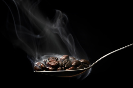 twirl: Scooping hot coffee beans with spoon. Stock Photo