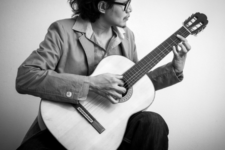 black guy: Man playing classical guitar. Black and white photo.