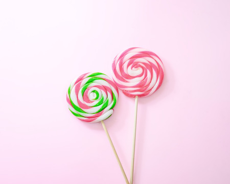 punctuate: Lollipop on pink background.,Pastel tone.