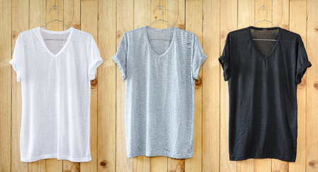 White T-shirt, Black T-shirt and Gray T-shirt hang on wood wall.