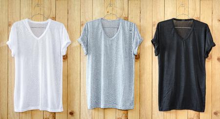 White T-shirt, Black T-shirt and Gray T-shirt hang on wood wall. Stock fotó - 58522181