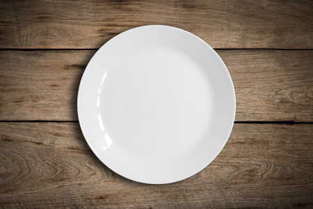 Blank white dish on a wood background. Stock fotó - 58522184