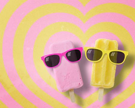 몇 가지 아이스크림 스틱 하트 패턴 핑크와 노란색 배경 복사 공간., 파스텔 톤에 선글라스를 착용. 스톡 콘텐츠