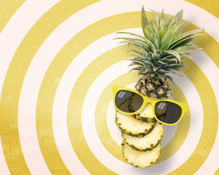 punctuate: Pineapple wearing sunglasses on circle pattern yellow and white background with copy space.,Pastel tone.