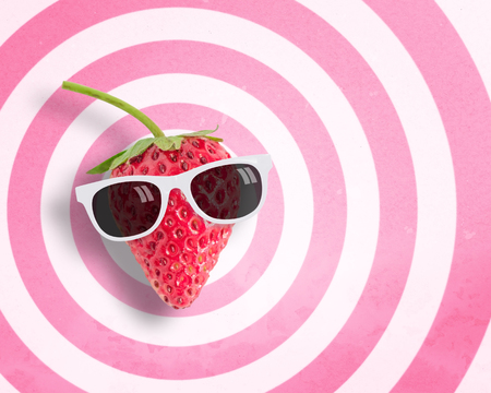 punctuate: Strawberry wearing sunglasses on circle pattern pink and white background with copy space.,Pastel tone. Stock Photo