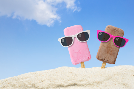 Couple ice cream wearing sunglasses on beach with copy space. Stock Photo