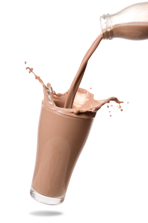 Pouring chocolate milk from bottle into glass with splashing., Isolated on white background.