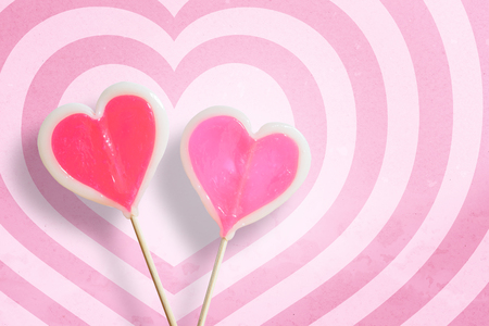 punctuate: Couple lollipop on hearts pattern pink and white background with copy space.,Pastel tone.