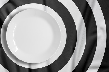 punctuate: Top view of empty food plate put on tablecloth., The tablecloth is stripe pattern punctuate black and white with copy space.