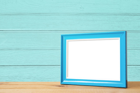mirror image: Blue picture frame put on wood table in blue wood wall room.