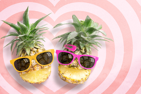punctuate: Couple pineapple wearing sunglasses on hearts pattern pink and red background with copy space and pastel tone. Stock Photo