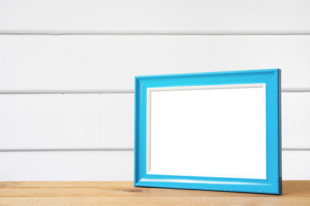 Blue picture frame put on wooden table in white wood wall room.