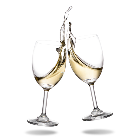 Cheers white wine with splash out of wineglass isolated on white background. Stock Photo