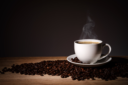 Steaming coffee in cup put on coffee beans on wood background with copy space.