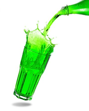 Pouring green soda from bottle into glass with splashing isolated on white background. 版權商用圖片