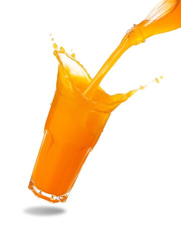 Pouring orange juice from bottle into glass with splashing isolated on white background.