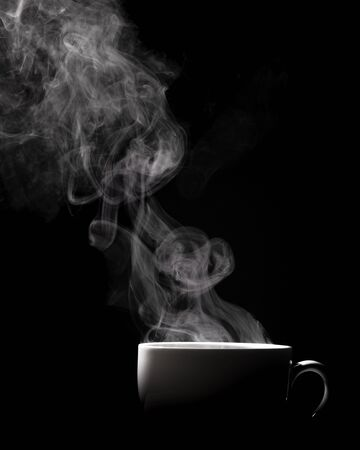 Steaming coffee in cup isolated on black background with copy space. Stockfoto