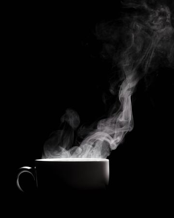 Steaming coffee in cup isolated on black background with copy space. 版權商用圖片