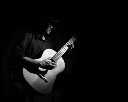 Man playing classical guitar. Black and white photo with copy space. 版權商用圖片