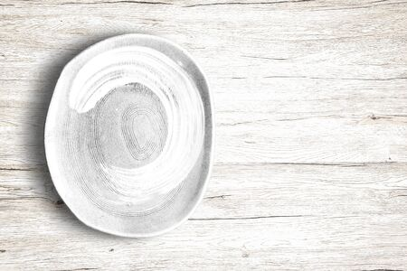 Top view of empty white food dish on a wooden background. 版權商用圖片