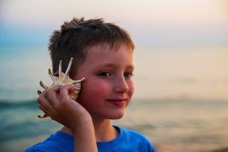 Young attractive boy on a beach holding a sea shell against his ear and listening to the sound of waves smiling