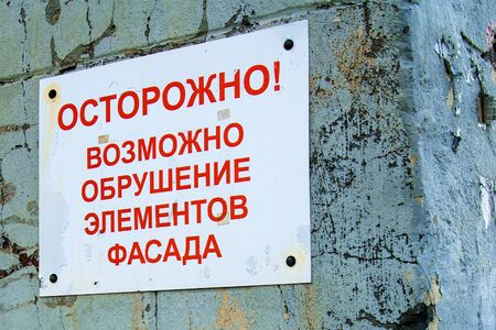 Empty plate on an old brick wall, restoration of an old building. Russian text carefully collapse of the facade.