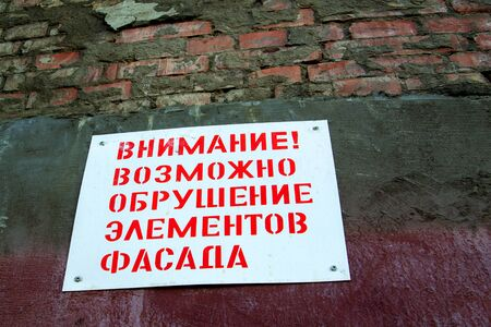 plate on an old brick wall, restoration of an old building. Russian text carefully collapse of the facade