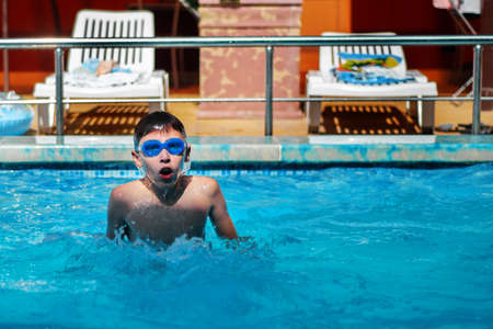 A little boy actively swims in the pool in the open air. The concept of sport and healthy lifestyle.