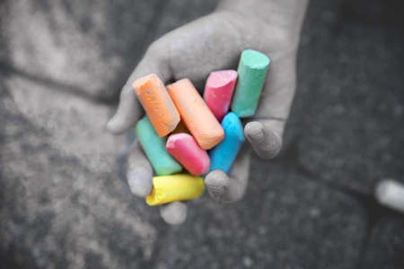 Hand holds colored chalk. Sad depressive photograph. Depression and bad mood concept.