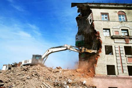 excavator demolishing a brick building. Machinery Demolishing Building.