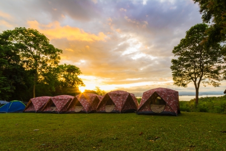 The sun is shining above camping tents in a morning day photo