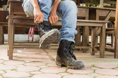 vistiendose: hombre en pantalones vaqueros se viste botas Foto de archivo