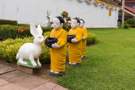 thialand: statue of monk in buddhist recieve food in thialand temple