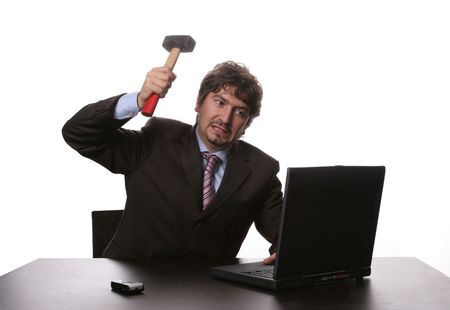 Fustrated businessman in his office threatening to destroy his PC with a hammer out of sheer frustration