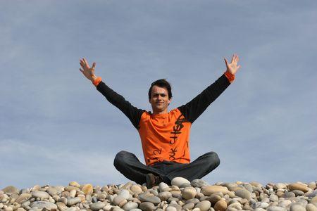 arms wide: casual giovane uomo a braccia aperte in spiaggia  Archivio Fotografico