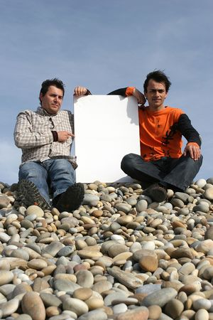 Two Young Men Holding White Card at the beach photo
