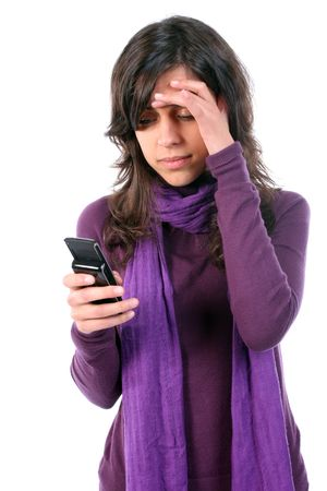 Young tired and with headache, reading a sms on her cellphone, isolated on white background photo