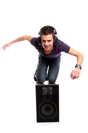 Young man with headphones, seating in a speaker, isolated in white background photo