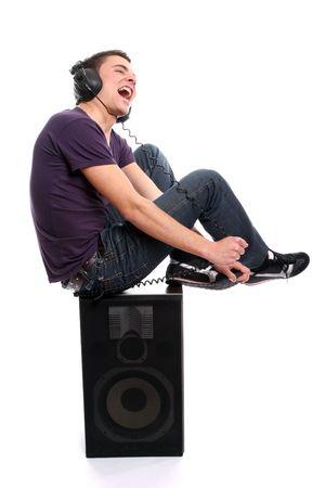 listening music: Casual hombre joven escuchando m�sica, aislados en fondo blanco Foto de archivo