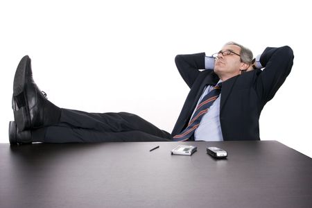 Successfull businessman relaxing over his desk, isolated in white background photo